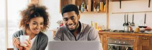 black couple at kitchen table on computer
